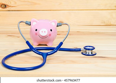 Piggy Bank and Stethoscope in wooden room.