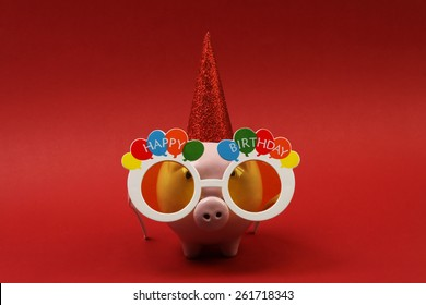 Piggy bank with sunglasses Happy birthday, party hat on red background-horizontal
