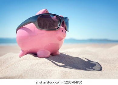 Piggy bank with sunglasses on the beach at the seaside in Summer