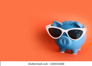 Piggy bank with sunglasses on color background, space for text. Travel agency
