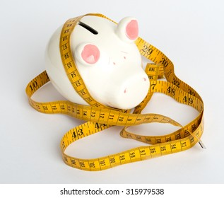 Piggy bank with tape measure on isolated white background, close up view