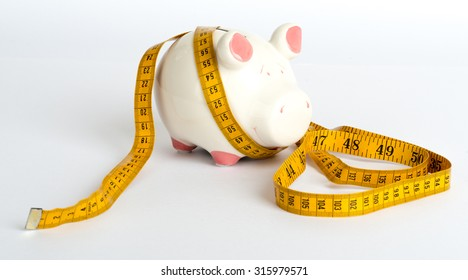 Piggy bank with tape measure on isolated white background, side view