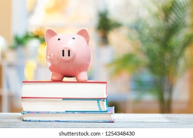 Piggy bank and textbooks education expense theme on a bright room background