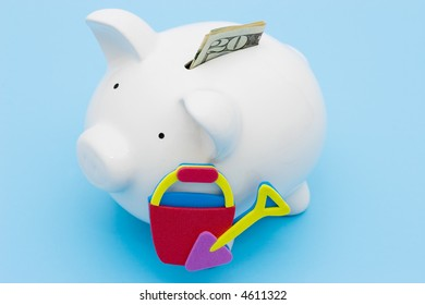 A piggy bank with a twenty dollar bill with a beach bucket and shovel