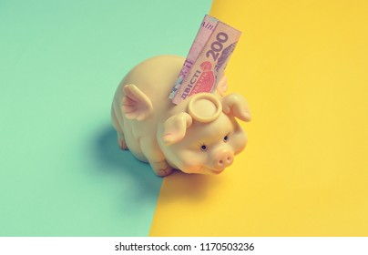 Piggy bank with two hundred hryvna bills on a yellow blue background. Ukrainian economy, Ukrainian flag