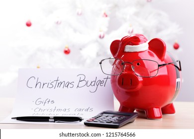 Piggy bank wearing glasses and Santa hat with a Christmas budget plan