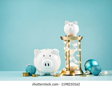 Piggy banks, christmas decorations and hourglass wrapped in lights on a blue background.