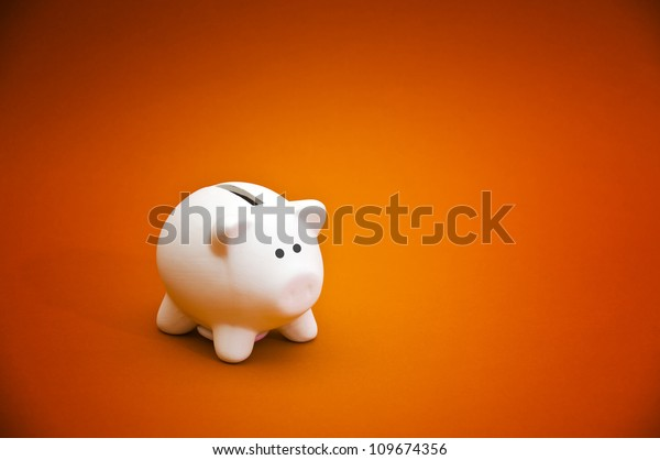 Piggy coin bank on orange background for money savings, financial security or personal funds concept.