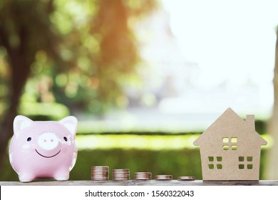 Piggy pink bank, money coins stacked on each other in different positions, house in paper model on the wooden table outdoor. Credit financial growing Loan to buy real asset concept. Saving money