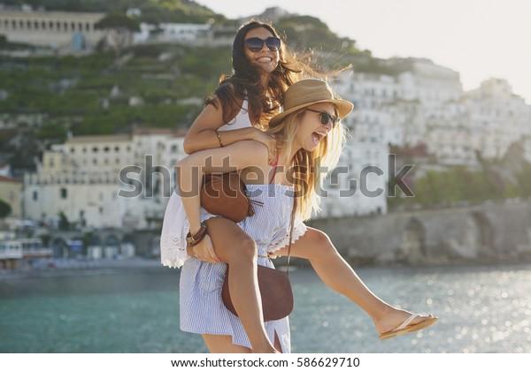 Piggyback happy tourist friends having fun on summer travel adventure vacation laughing
