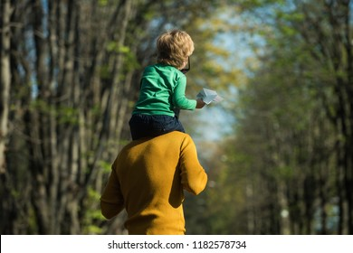 Piggyback ride. Father hold little son on shoulders giving child piggyback in park. Relax you are with me.
