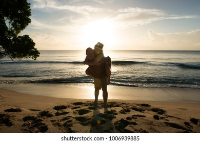 Piggybacking couple on the beach with sun setting behind them