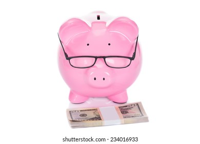 Piggybank with dollar bundle isolated over white background