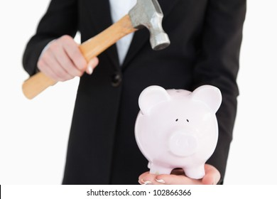 Piggy-bank going to be break with a hammer against white background