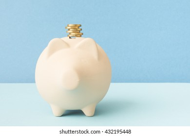 Piggybank and golden coins with blue background. Concept of saving money, financial investment and economy.