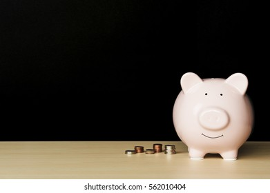 Piggybank on wooden table. Piggy bank has stacks of coins next to it.