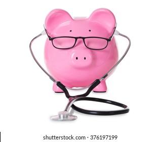 Piggybank with stethoscope and eyeglasses isolated over white background
