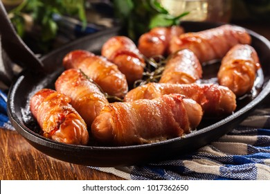 Pigs in blankets. Mini sausages wrapped in smoked bacon in baking dish