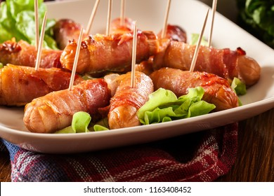 Pigs in blankets. Mini sausages wrapped in smoked bacon on a plate