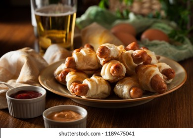 Pigs in blankets. Mini sausages wrapped in puff pastry. Dark mood