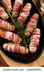 Pigs in blankets. Raw mini sausages wrapped in smoked bacon ready to baked. Top view