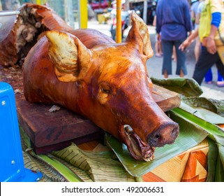 The pig's head. Roasted pork head. Barbecue cooked pork in public eatery. Wedding or open air dish. Whole baked pig image. Culinary illustration. Traditional pork or jamon dish. Tasty meat from fire