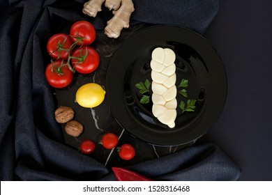 Pigtail cheese on a black plate, decorated with cherry tomatoes, walnuts, white cloth. on black background. The concept of cheese products.