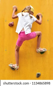 A pigtailed girl in a white T-shirt and pink shorts climbs the yellow wall of a children's climbing wall