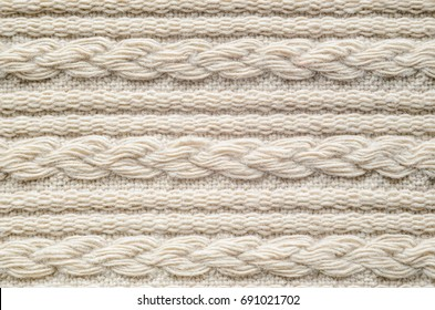 Pigtails on Beige Knitwear Fabric Texture. Machine Knitting Texture Macro Snapshot. Beige Knitted Background.
