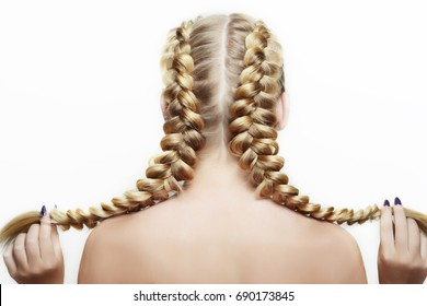 pigtails on a head wickerwork of hairs to the girl hair-do  blonde on the white background of favour of hairdresser