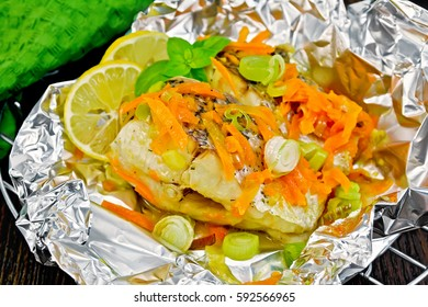 Pike with carrots, leek, basil and slices of lemon in foil on the lattice, towel on a background of dark wood planks