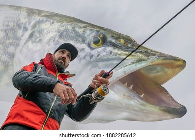 Pike fishing. Angler in action, fisherman catch muskie fish by spinning rod on blurred muskellunge background. Soft focus - Shutterstock ID 1882285612