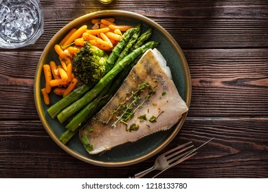 Pike perch fillet with asparagus, broccoli and carrots. Fried fish with stewed greens.