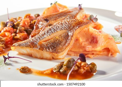Pike perch or zander fillet with a side dish of tomatoes and capers served on a round platter. Restaurant main course with fried sander fish or barbecue pike meat on white plate isolated