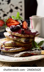 pikelets with fresh blueberries and strawberries, dusted with icing sugar and toped with a sauce. selective focus