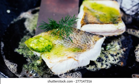 Pike-perch fillet with herbs are fried in butter in a frying pan.