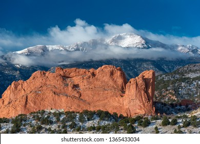 Pikes Peak enshrouded in clouds soaring above the Garden of the Gods at Colorado Springs, Colorado
