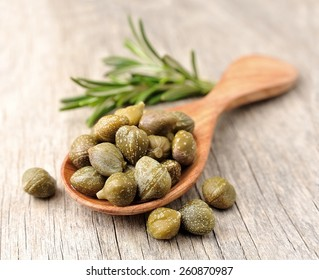 Pikled capers on wooden texture.
