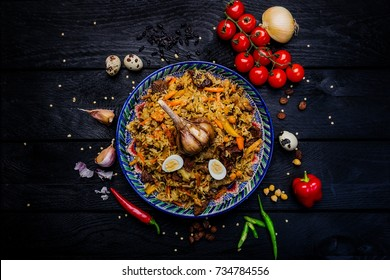 Pilaf and ingredients on plate with oriental ornament on a dark wooden background. Central-Asian cuisine - Plov Top view