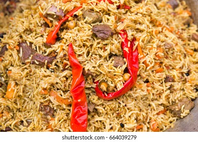 Pilaf with pieces of meat and red hot pepper closeup