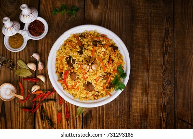 pilaf in a plate on wooden background, top view, copy space -