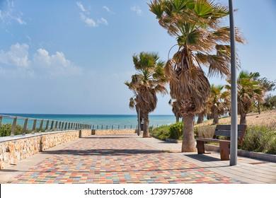 Pilar de la Horadada empty paved promenade near Mediterranean Sea during windy weather, no people sunny warm day. Tourism and holiday, summer vacation concept. Alicante, Costa Blanca, Spain