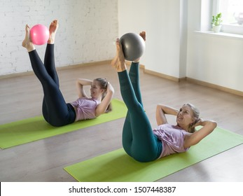 Pilates abs exercise with small fit ball. Two pretty girls lying on mats and raise up her legs doing workout in fitness studio, selective focus. Gymnastics, yoga, group training, abdominal, healthy
