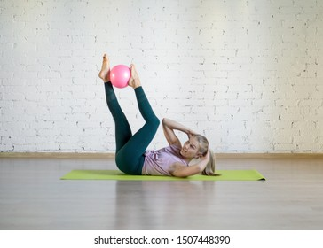 Pilates abs exercise with small fit ball. Caucasian woman doing workout in fitness studio. Gymnastics, yoga, abdominal, healthy spine, sport, smart body and wellness concept