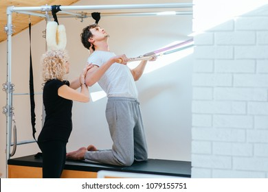Pilates aerobic female instructor workout with fit man in cadillac fitness exercise. Active and healthy lifestyle rehabilitation concept.