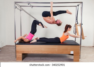 Pilates aerobic instructor a group of three people in cadillac fitness exercise.