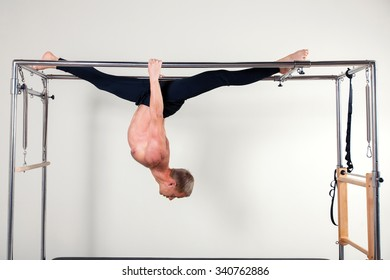 Pilates aerobic instructor man in cadillac fitness exercise. acrobatic upside down balance