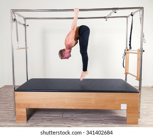 Pilates aerobic instructor man in cadillac fitness exercise.