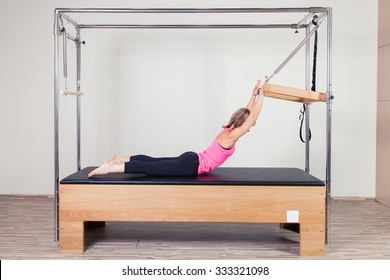 Pilates aerobic instructor woman in cadillac fitness exercise.