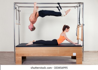 Pilates aerobic instructor woman and man  in cadillac fitness exercise.